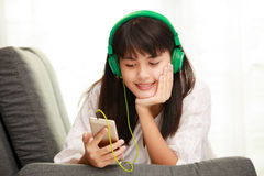 Young Asian girl listening to music with headphone and smarthpho Royalty Free Stock Photography