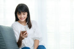 Young Asian girl listening to music with headphone and smarthpho Royalty Free Stock Images