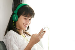 Young Asian girl listening to music with headphone and smarthpho Stock Photography