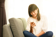 Young Asian girl listening to music with headphone and smarthpho Royalty Free Stock Photo