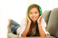 Young Asian girl listening to music with headphone and smarthpho Royalty Free Stock Image