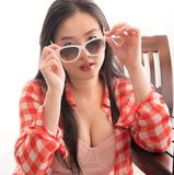 Young Asian girl looks at the camera over her sunglasses. An attractive and pretty young woman lifts her sunglasses and eyes the camera while wearing a bold stock photography