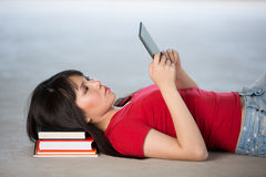 Young Asian girl lying on floor holding a Reader. Royalty Free Stock Images