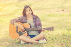 Young asian girl playing guitar. In the garden Royalty Free Stock Photo