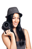 Young asian girl posing with a camera. A young asian girl posing and smiling with an SLR camera Royalty Free Stock Photography