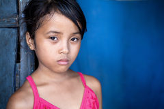 Young Asian girl in poverty over blue stock image
