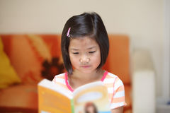 Young asian girl reading a book Royalty Free Stock Image