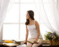 Young asian girl reading book in front of window Stock Photography