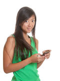 Young asian girl sending a message with her mobile Royalty Free Stock Photo