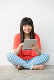 Young Asian girl sitting holding a Digital Tablet. Royalty Free Stock Photo