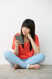 Young Asian girl sitting holding a Reader. Stock Images