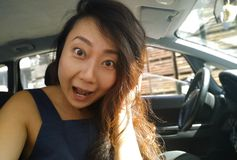 Young asian girl sitting inside of a car and surprised looking at camera. royalty free stock image