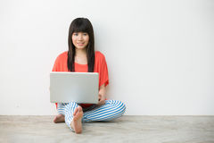 Young Asian girl sitting using laptop Royalty Free Stock Image