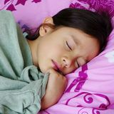 Young Asian Girl Sleeping. A young Asian girl holds on securely to her soft green cardigan as she sleeps on her bed Royalty Free Stock Photo