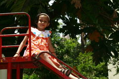 Young Asian girl on slide Royalty Free Stock Images