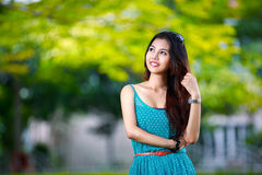 Young asian girl at summer green park. Outdoor stock photography