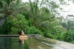 Young Asian Girl swimming in the infinity pool with beautiful view royalty free stock photos