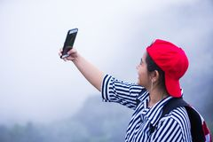 Young asian girl take her self portrait. Young asian girl with red hat take her self portrait, selfie by her mobile phone. At outdoor park with fog and cloud Royalty Free Stock Photos