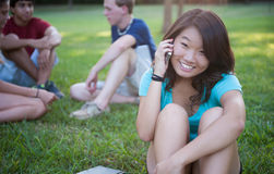 Young Asian girl talking on phone outside. A young Asian girl talking on phone outside with friends in the background Royalty Free Stock Images