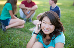 Young Asian girl talking on phone outside. A young Asian girl talking on phone outside with friends in the background Royalty Free Stock Photos