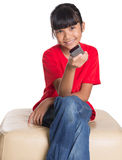 Young Asian Girl With TV Remote IV Stock Photos
