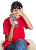 Young Asian Girl With TV Remote IX Stock Photos