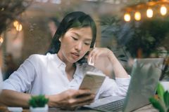 Young Asian girl using phone at a coffee shop with a laptop view through glass stock photo
