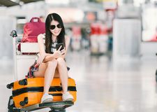 Young Asian girl using smartphone, waiting for flight at airport, sitting on baggage trolley or luggage cart Royalty Free Stock Photo