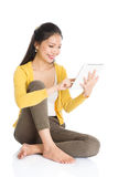 Young Asian girl using tablet pc. Full length portrait of casual Asian girl sitting on floor smiling and using touch screen tablet pc, isolated on white Stock Photos