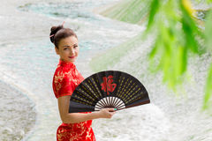 Young Asian girl walking in national dress. With a fan near the river Stock Photos
