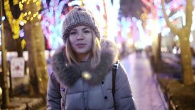 A young Asian girl woman walks along a street park, with trees, lit up with colored garlands. A young Asian girl walks along a street park, with trees, lit up stock footage