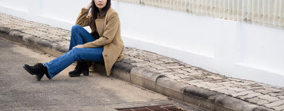 Young asian girl woman wearing blue jeans and brown jacket near building. Pretty young asian girl woman wearing blue jeans and brown jacket near building Stock Photo