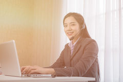 Young Asian girl working at a laptop in a small medium enterprise Stock Image