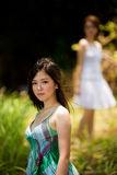 Young asian girls outdoor. Young asian girl outdoor with one out of focus girl looking to toward the in focus girl Stock Photos