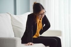 Woman having stomach ache. Young Asian glasses business woman sitting on sofa and suffering from stomach ache. Illness, diseases concept stock images