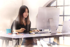 Young asian graphic designer working on computer. Using digital tablet at office Royalty Free Stock Photos