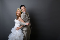 Young asian groom and bride posing and smiling in studio for pre Royalty Free Stock Images