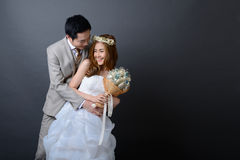 Young asian groom and bride posing and smiling in studio for wed Royalty Free Stock Image