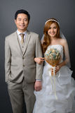 Young asian groom and bride posing in studio for pre wedding sho. T Royalty Free Stock Images