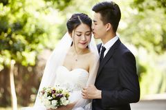 Outdoor portrait of a newly-wed asian couple. Young asian groom kissing bride outdoors during wedding ceremony Royalty Free Stock Photos