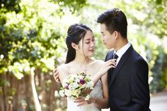 Outdoor portrait of a newly-wed asian couple royalty free stock photo