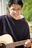 Young Asian Guitar Player Royalty Free Stock Images