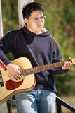 Young asian guitar player Stock Photography