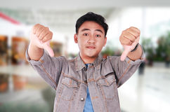 Young Asian Guy Mocking Gesture with Thumbs Down Stock Photo