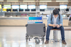 Young asian guy waiting for airport check in Royalty Free Stock Photography