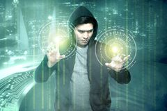 Young asian hacker in black hoodie touching virtual screen with binary code. Over digital background stock photography
