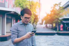 Young asian handsome businessman concentrated while reading his. Smartphone. Portrait of asian business man reading message with smart phone in outdoor stock photography