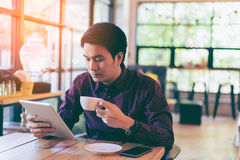 Young asian handsome businessman concentrated while reading his. Tablet with a cup of coffee and smartphone in coffee cafe. Portrait of asian business man royalty free stock image