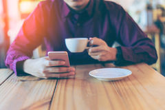 Young asian handsome businessman smiling while reading his smart. Phone with a cup of coffee in coffee cafe. Portrait of asian business man reading message with stock image