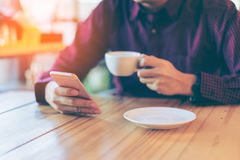 Young asian handsome businessman smiling while reading his smart. Phone with a cup of coffee in coffee cafe. Portrait of asian business man reading message with royalty free stock photo